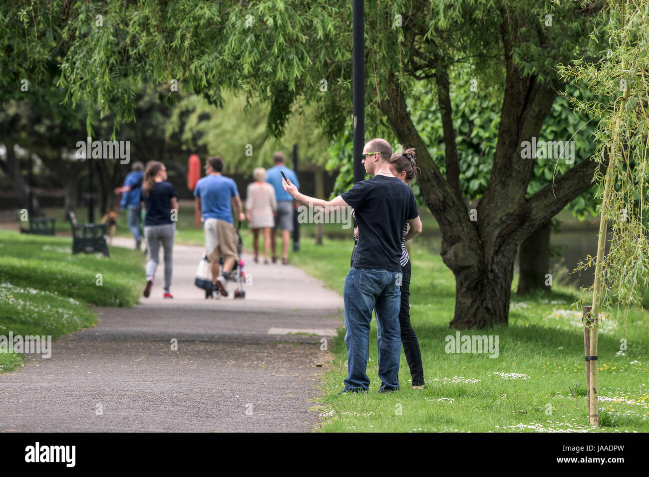A couple taking a selfie in a park. - Stock Image