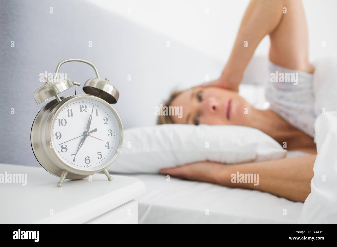 Blonde Woman Covering Her Ears From Alarm Clock Noise In Bed At Home In  Bedroom