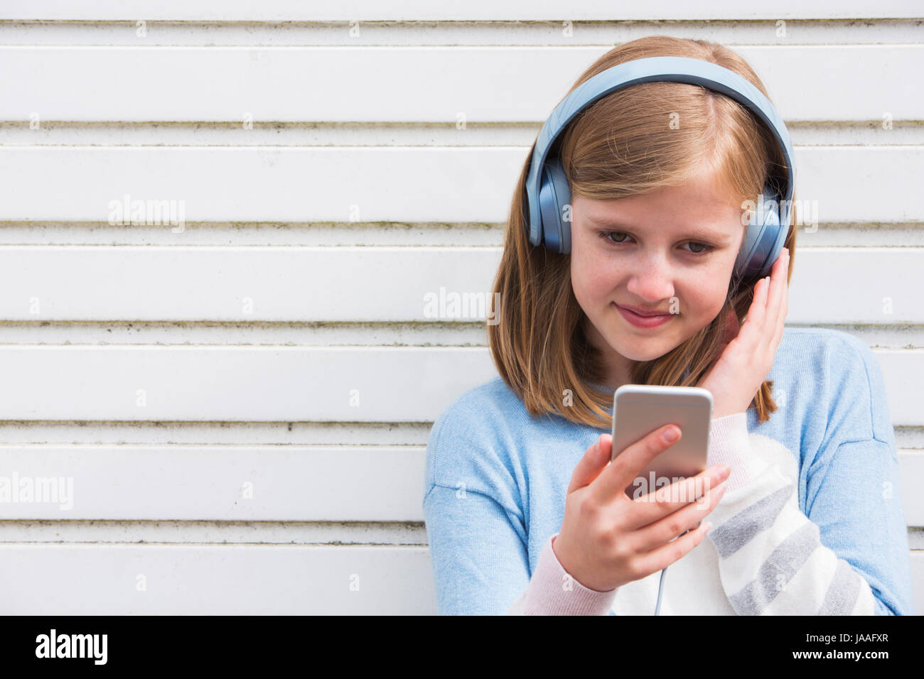 Pre Teen Girl Wearing Headphones And Listening To Music In Urban Setting - Stock Image