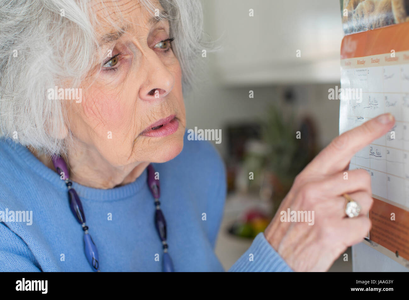 Confused Senior Woman With Dementia Looking At Wall Calendar - Stock Image