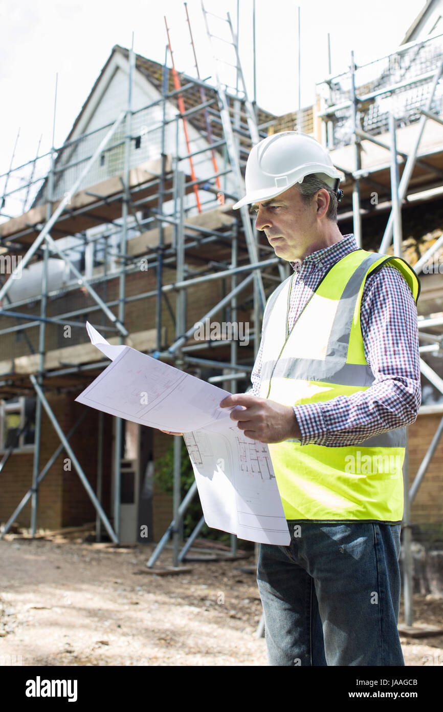 Architect On Building Site Looking At House Plans - Stock Image