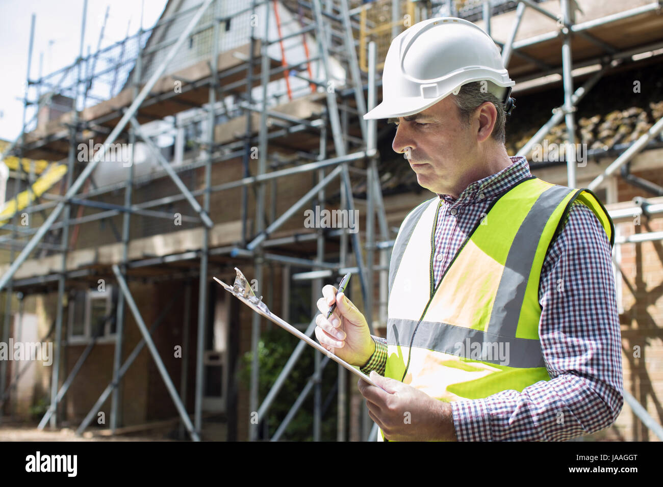 Building Inspector Looking At House Renovation Project - Stock Image