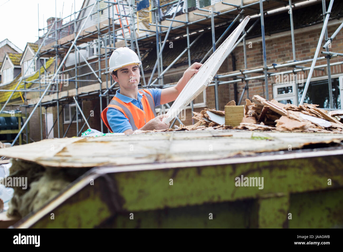 Builder On Site Putting Waste Into Rubbish Skip - Stock Image