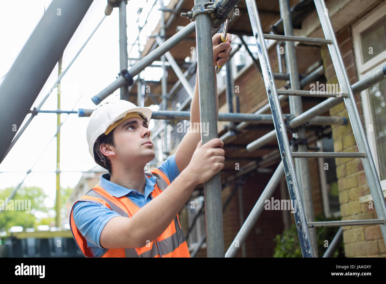 Builder On Site Putting Up Scaffolding - Stock Image