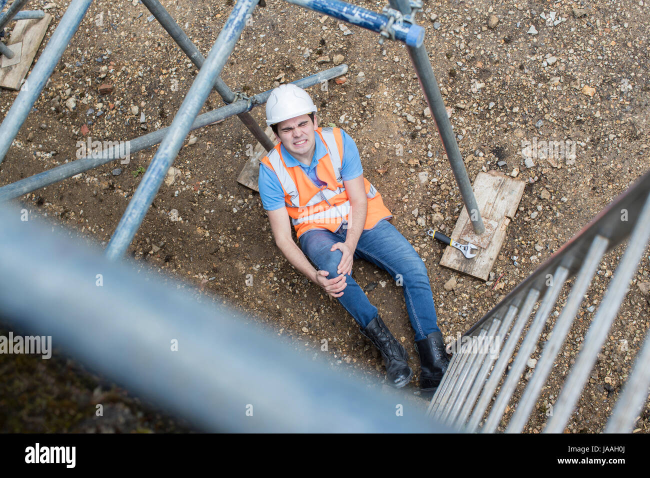 Construction Worker Falling Off Ladder And Injuring Leg - Stock Image