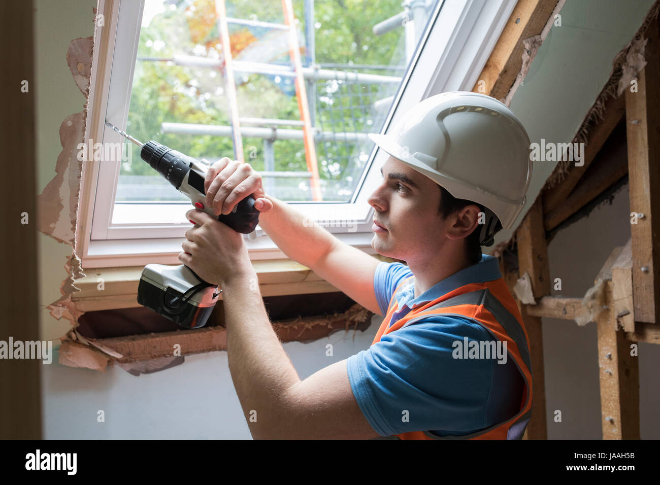 Construction Worker Using Drill To Install Replacement Window - Stock Image