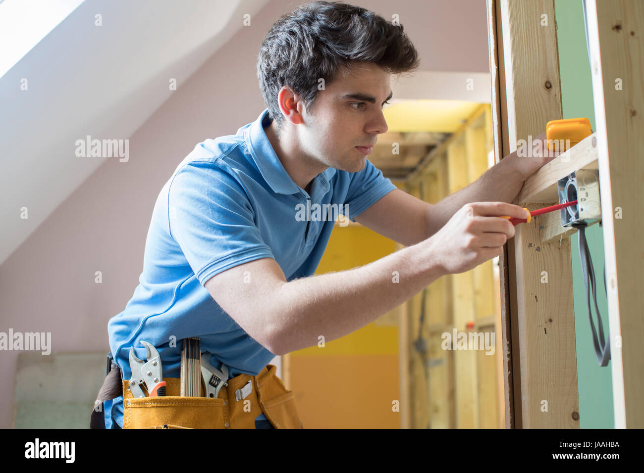 Electrician Installing Socket In New House - Stock Image