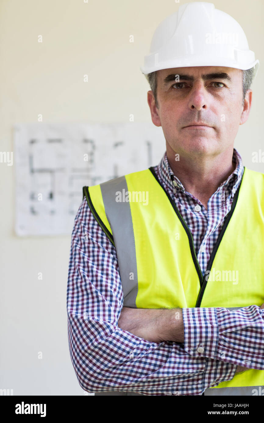 Portrait Of Architect Wearing Hard Hat With Plans In Background - Stock Image