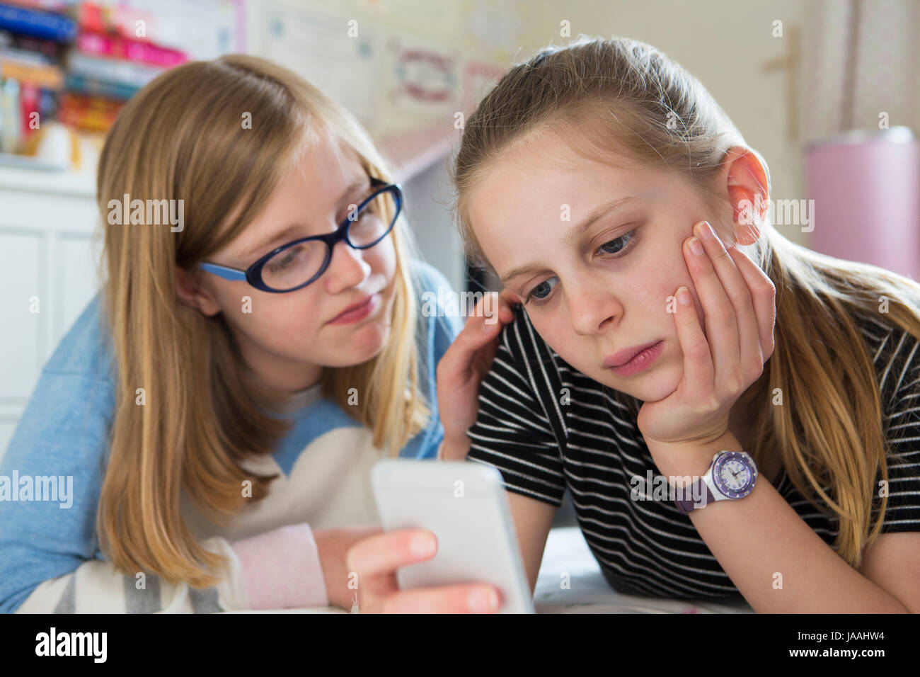 Pre Teen Girl With Friend Being Bullied By Text Message - Stock Image
