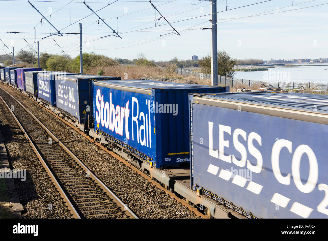 'Less CO2 Rail' container train heading north on the West Coast Main Line railway at Hest Bank, Lancashire. - Stock Image