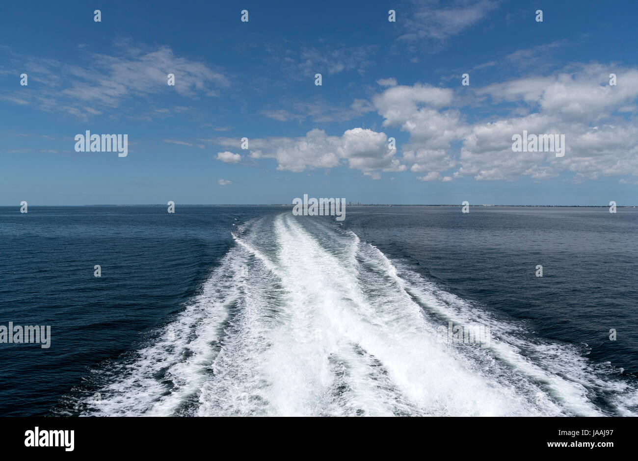 The wake of a high speed passenger ferry crossing Tampa Bay with a backdrop of St Petersburg Florida USA - Stock Image
