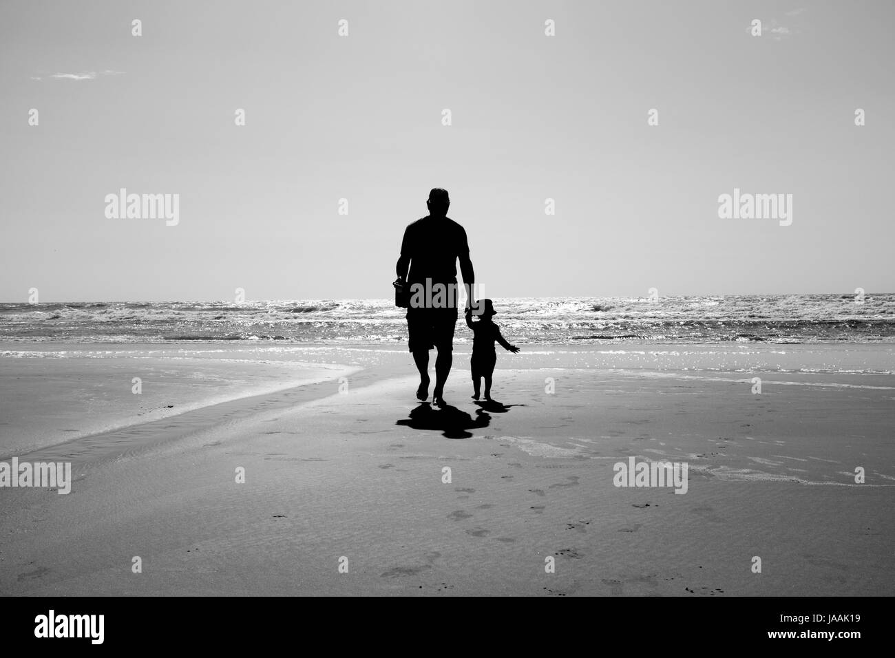 Silhouette of Man and Child Walking on the Beach - Stock Image