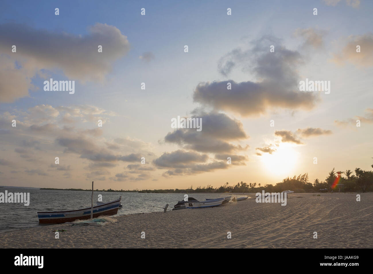 Sunset on the tropical island of mussulo angola with fishing boats - Stock Image