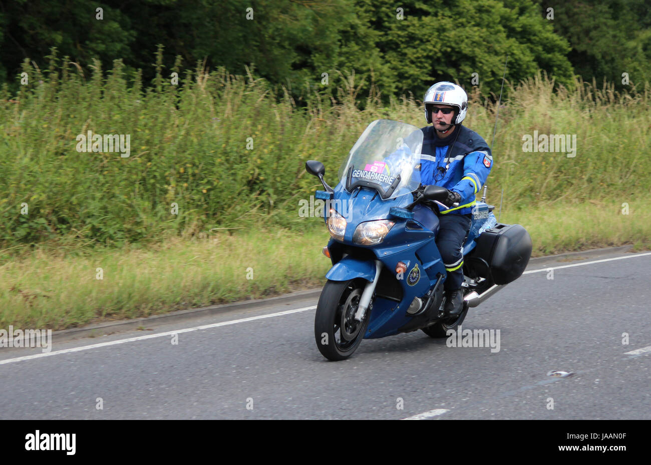 A French Gendarmerie motorcyclist riding along a British road, during stage 3 of the Tour de France, in 2014. - Stock Image