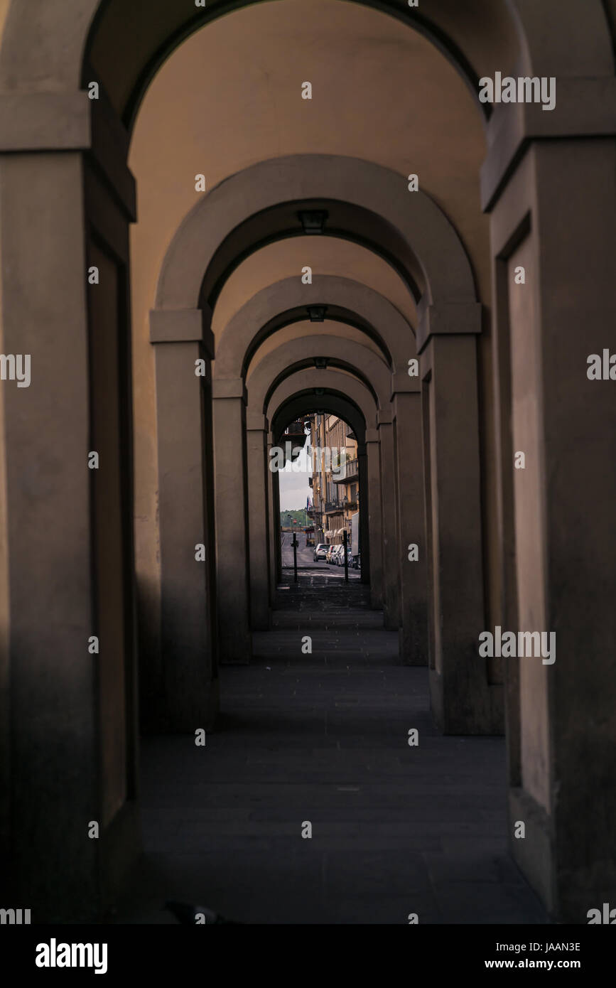 Series of arches along the Arno River in Florence with keyholed street scene. Stock Photo