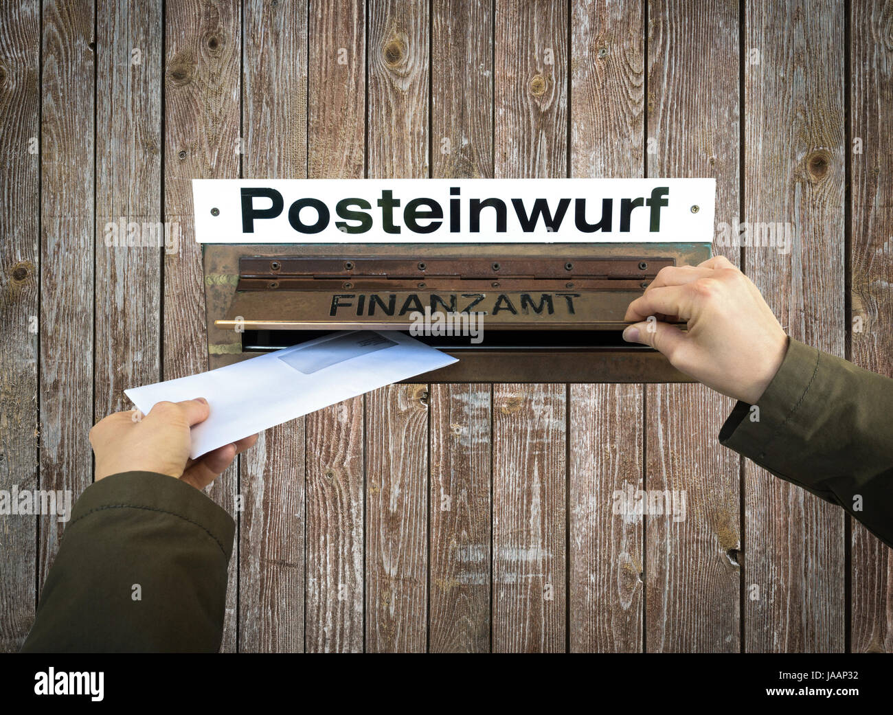 Hands post a letter into letterbox of finance office, Finanzamt. - Stock Image