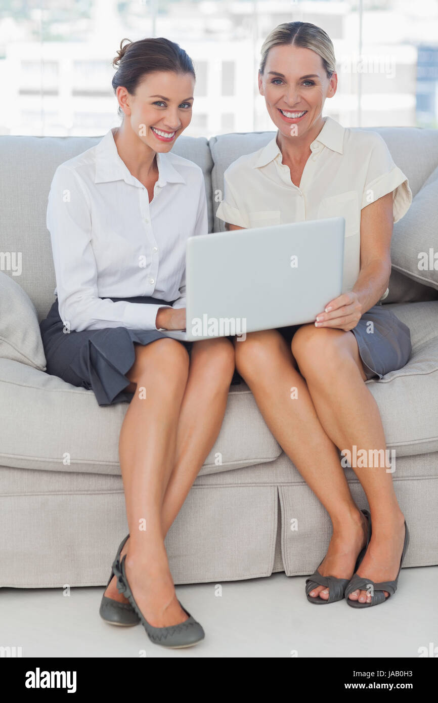 3caf7ecb7ffae0 Smiling businesswomen working together posing in bright office - Stock Image