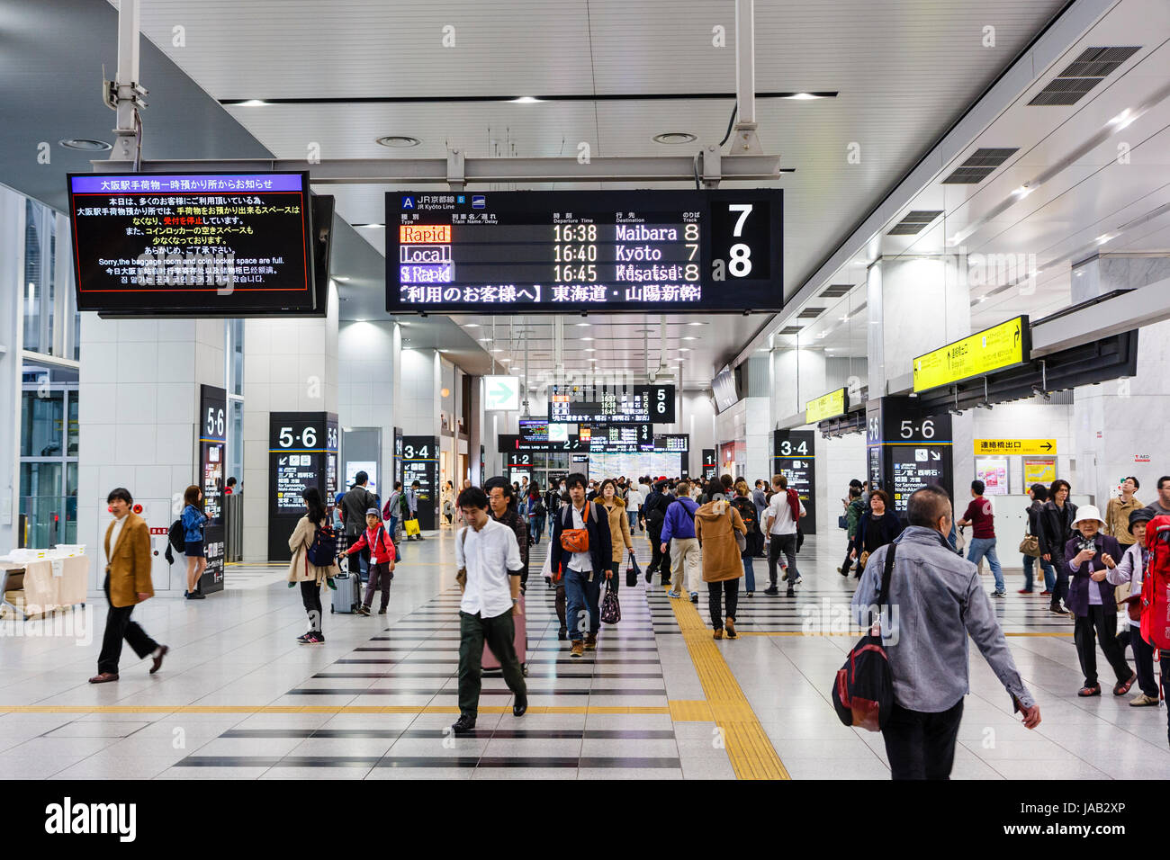 Osaka station, interior. Upper concourse with busy with people and commuters walking beneath overhead sign for trains - Stock Image