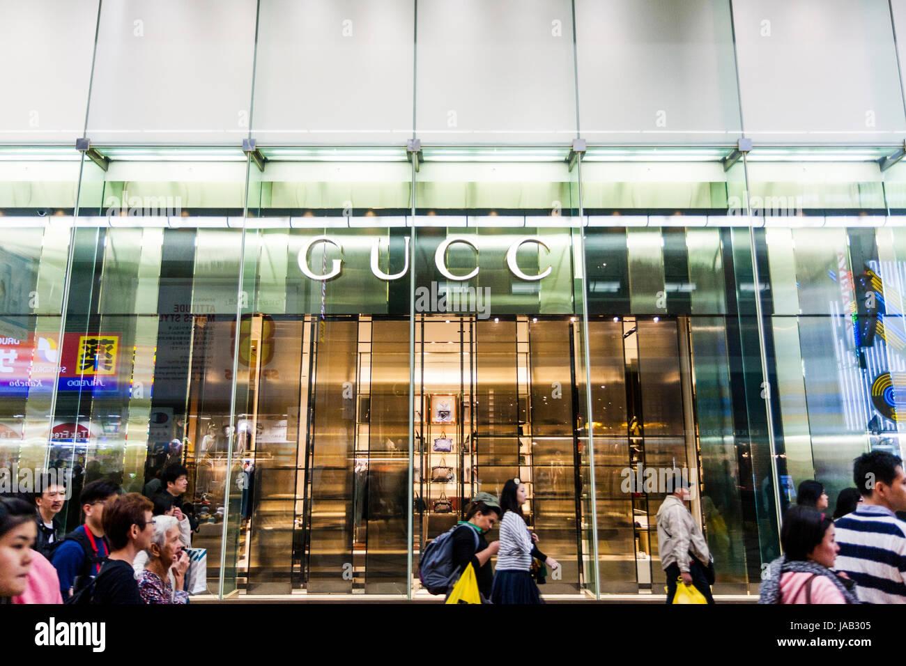 Japan, Osaka, Shinsaibashi. Gucci fashion store front. Green tinted glass with name above entrance. People walking - Stock Image