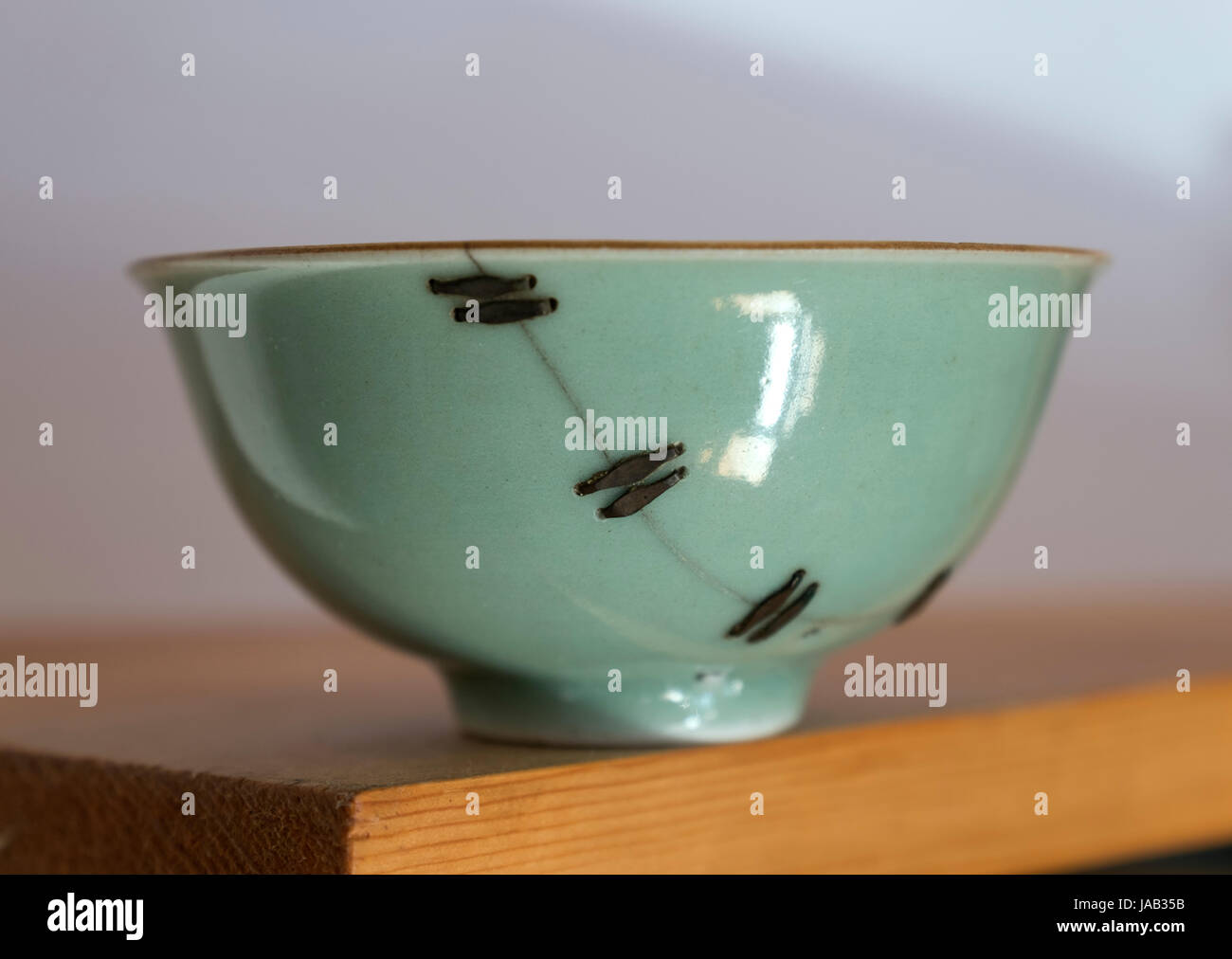 A broken porcelain bowl from Qing Dynasty  (1644–1912)  was repaired tightly with Chinese traditional Ju Ci handcraft. - Stock Image