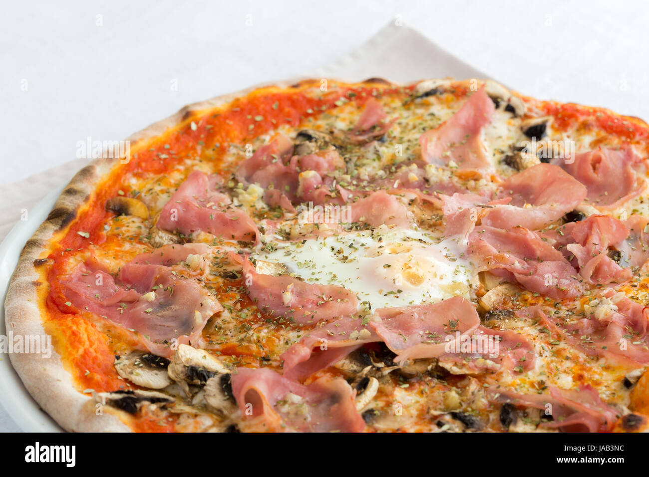 A pizza cappriciosa, its ingredients are tomatoes, mushrooms, an egg, ham and mozzarella. It is cooked on a wood - Stock Image