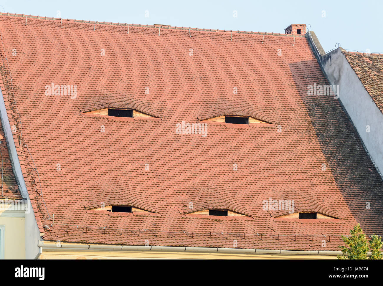 SIBIU, ROMANIA - AUGUST 10, 2016: Detail of houses situated near downtown of the city. Roof with eye windows - Stock Image