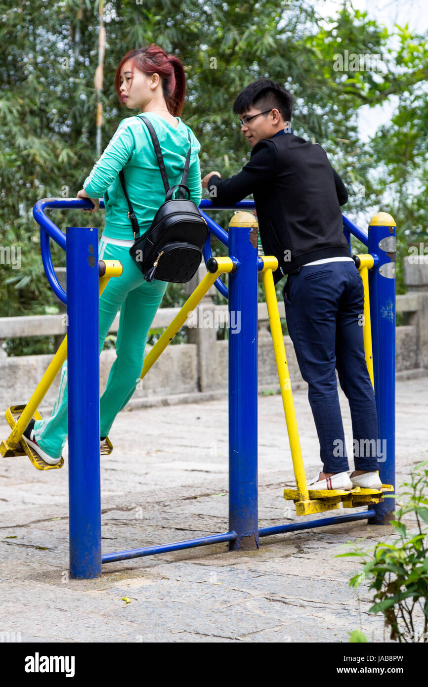 Yangshuo, China.  Young Couple Working Out on Public Exercise Equipment. - Stock Image