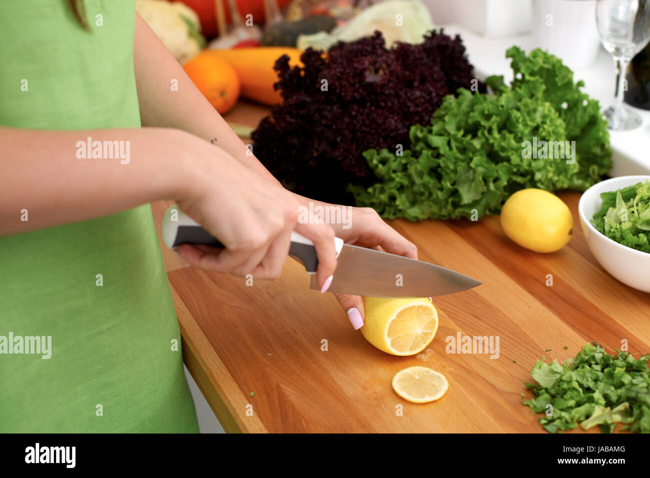 Closeup of woman hands cooking vegetables salad in kitchen. Housewife cuts lemon. Healthy meal and vegetarian concept. - Stock Image