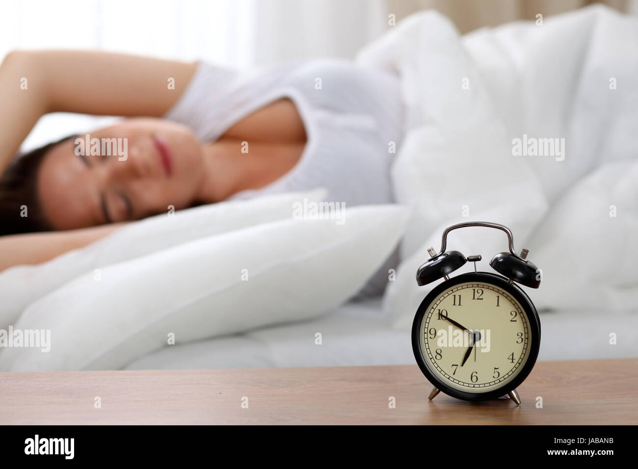 Alarm Clock Standing On Bedside Table Has Already Rung Early Morning To  Wake Up Woman In Bed Sleeping In Background. Early Awakening, Not Getting  Enough ...