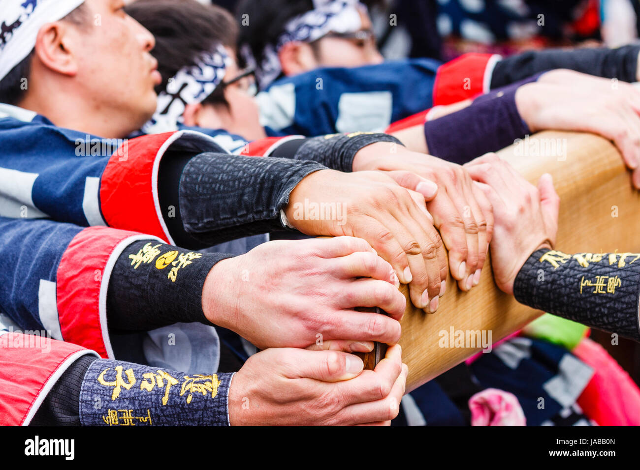 Close up of hands gripping wooden beam, part of Dashi float, as men struggle to pull it in one direction. Inuyama - Stock Image