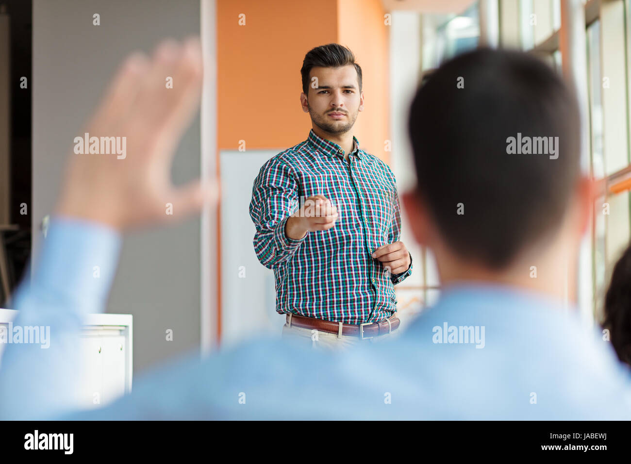 Business people Raising there Hand Up at a Conference to answer a question - Stock Image