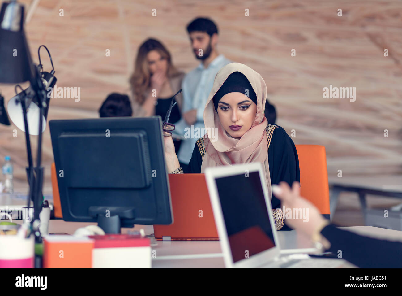 Young Arabic business woman wearing hijab,working in her startup office. - Stock Image
