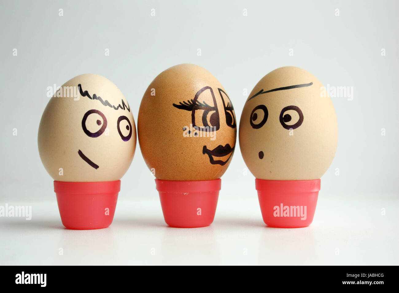 Eggs with painted face. Concept of love between white and black, love triangle. Photo for your design. - Stock Image