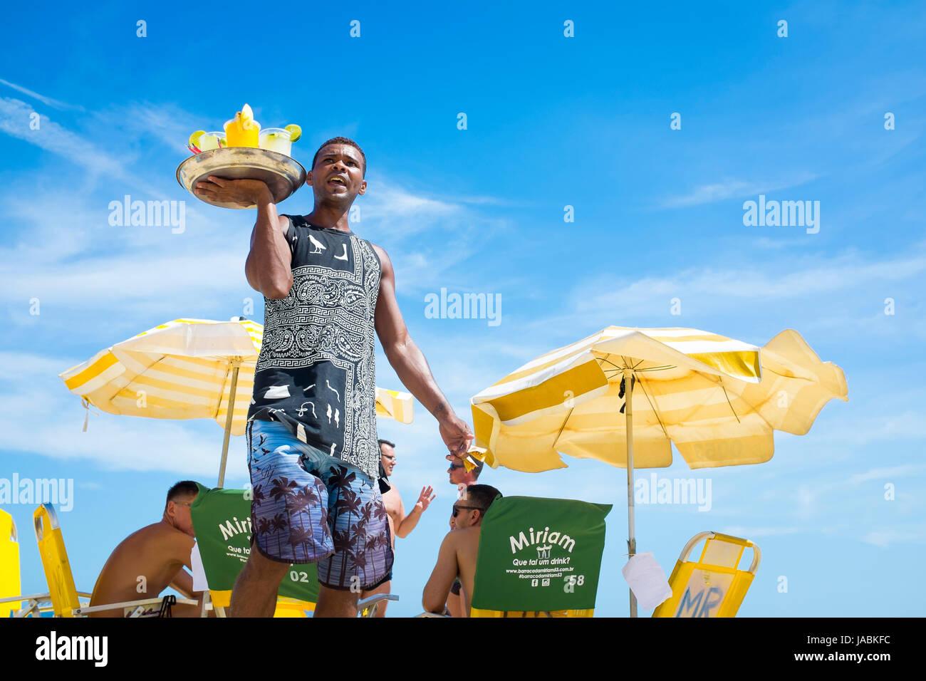 RIO DE JANEIRO - FEBRUARY 16, 2017: A beach vendor selling caipirinhas calls out to potential customers on Ipanema - Stock Image