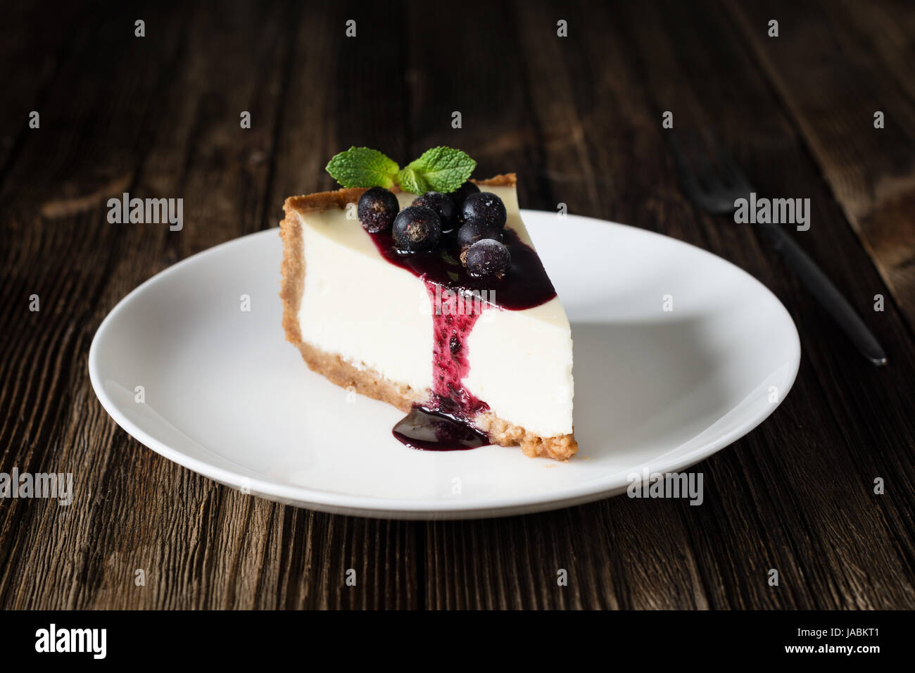 Piece of cheesecake with black currant and blueberry sauce on white plate on wooden table. Closeup view Stock Photo