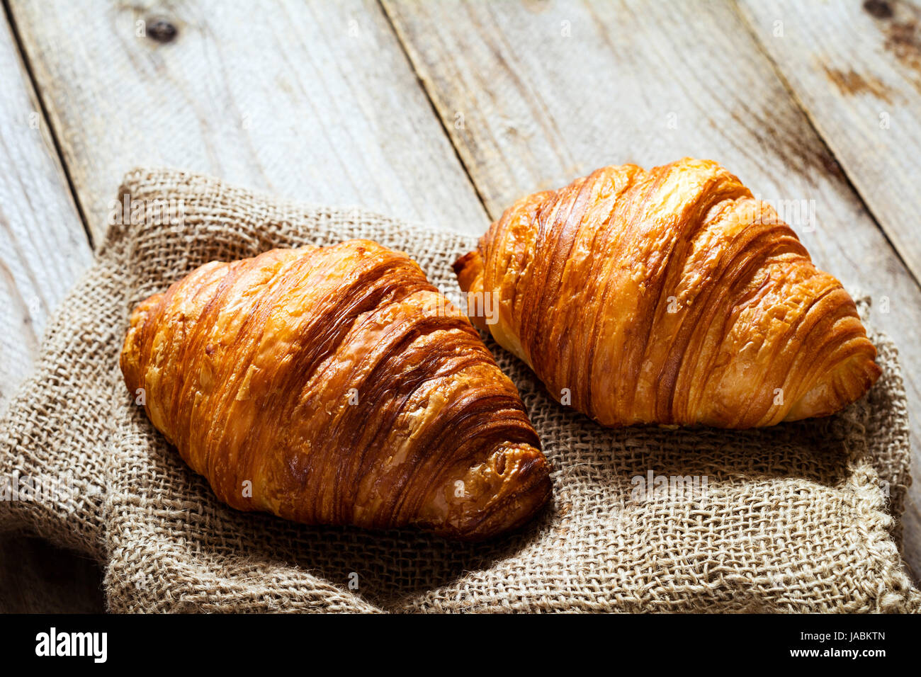 Two fresh croissants on burlap textile on rustic wooden table. Closeup view - Stock Image