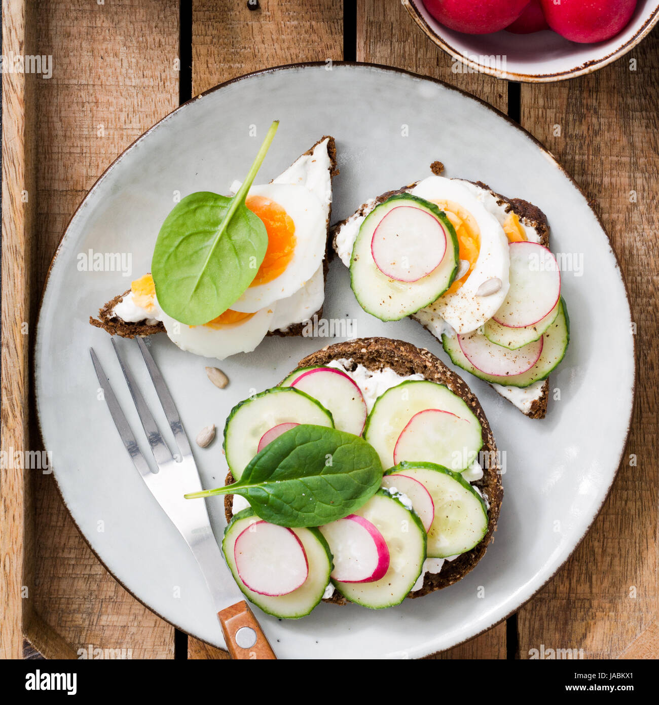 Fresh healthy toasts on plate. Top view of toasts with radish, cucumber, goat cheese, boiled egg and spinach. Square - Stock Image