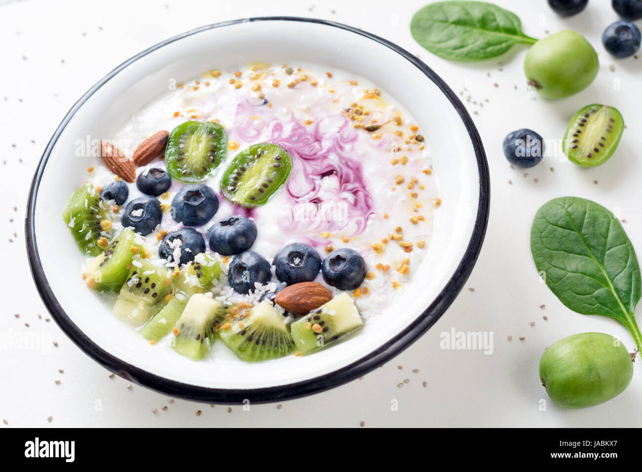 Smoothie bowl with acai berry, kiwi, blueberry, almond, coconut, bee pollen and baby spinach on white background. - Stock Image