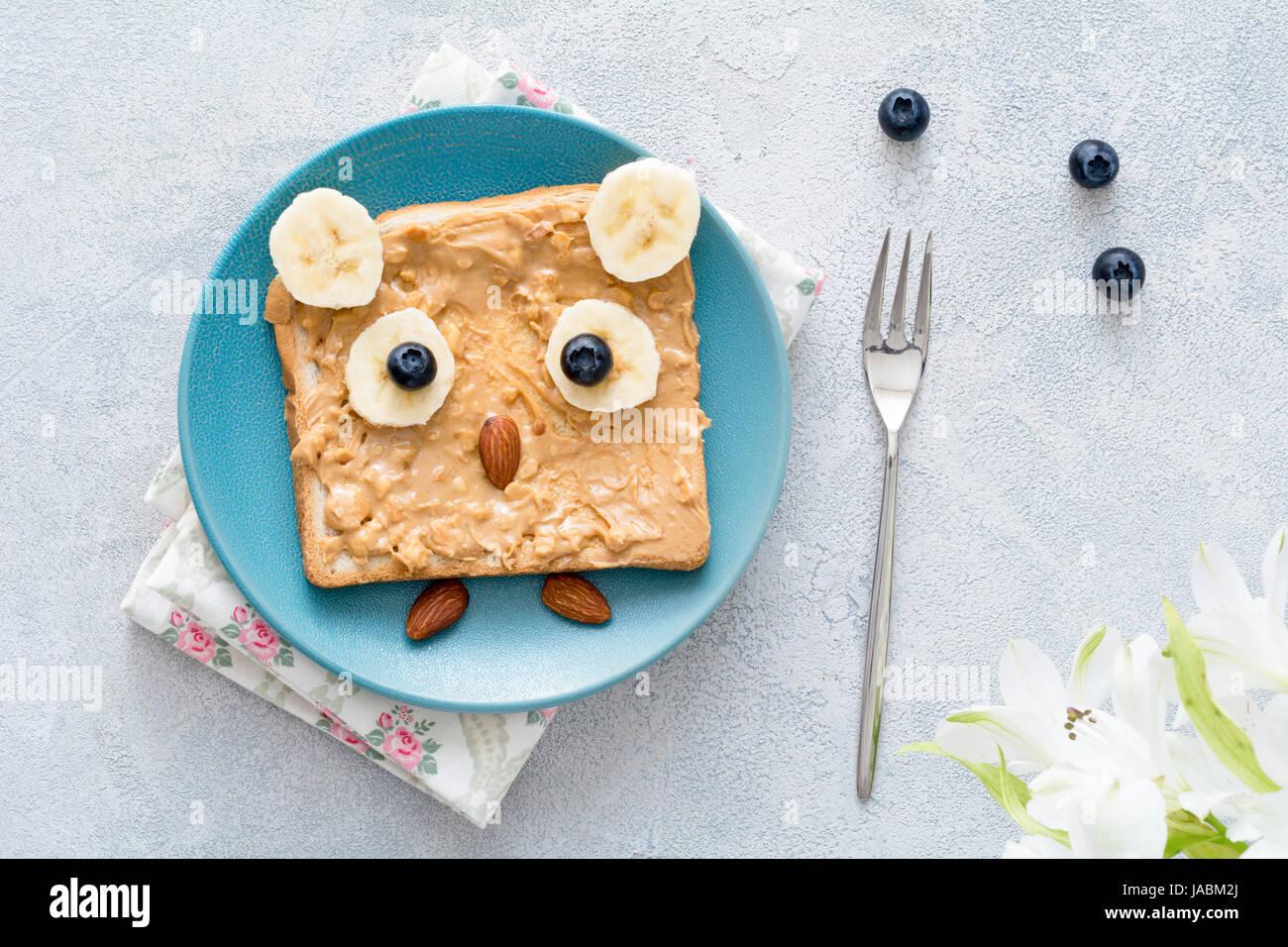 Peanut butter toast for kids healthy breakfast. Owl shaped funny breakfast food art Stock Photo