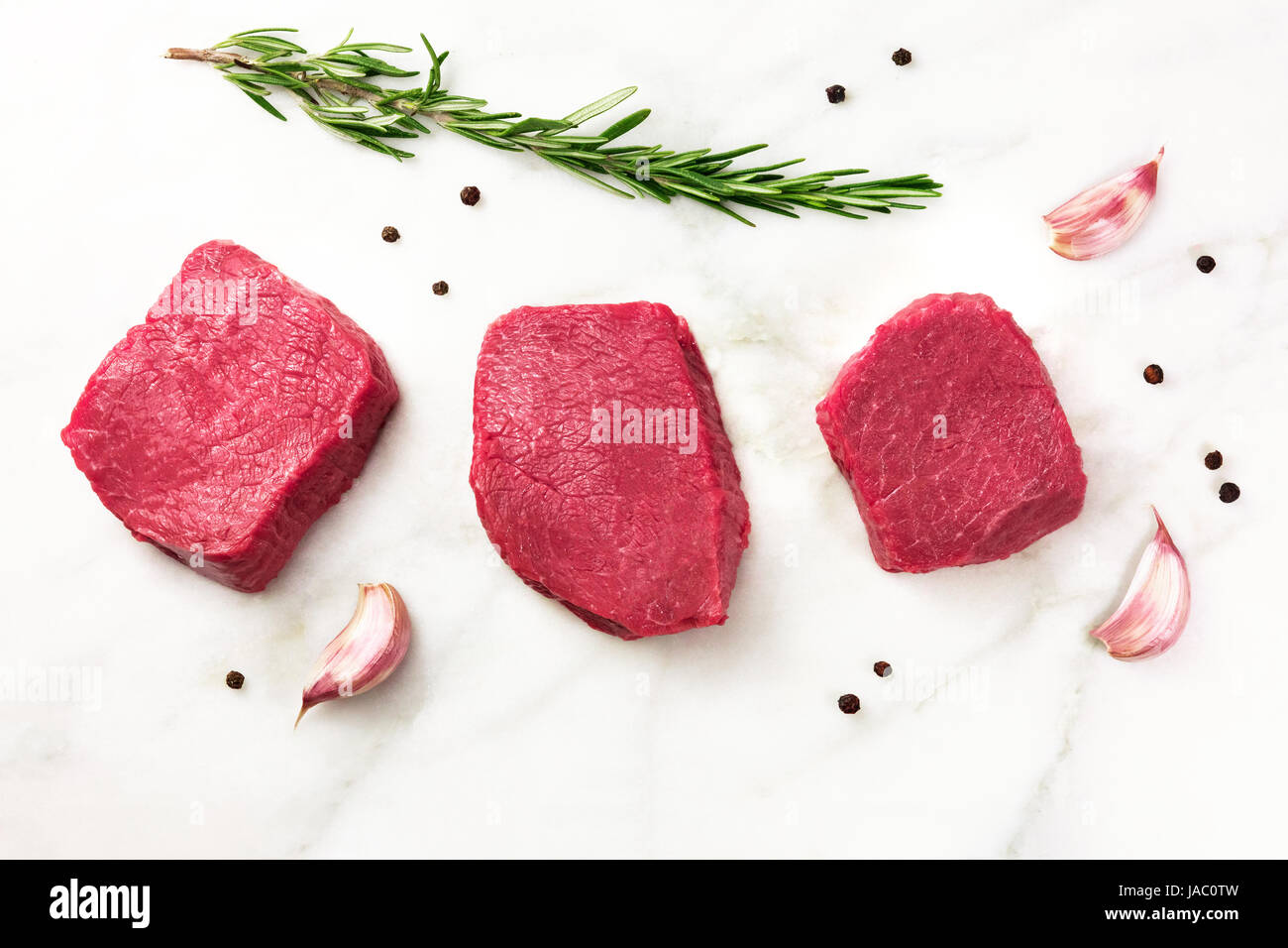 Three slices of raw meat with seasoning and copyspace - Stock Image