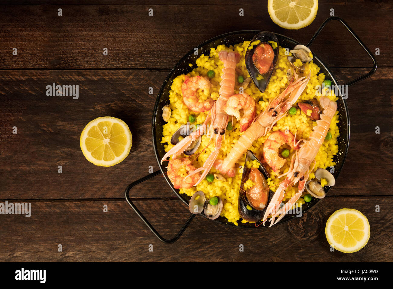 Spanish seafood paella in paellera, with lemons Stock Photo
