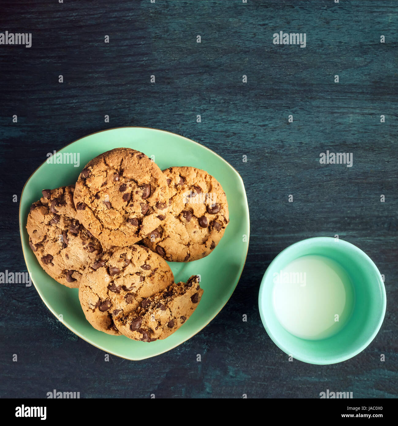 Chocolate chips cookies with glass of milk, shot from above - Stock Image