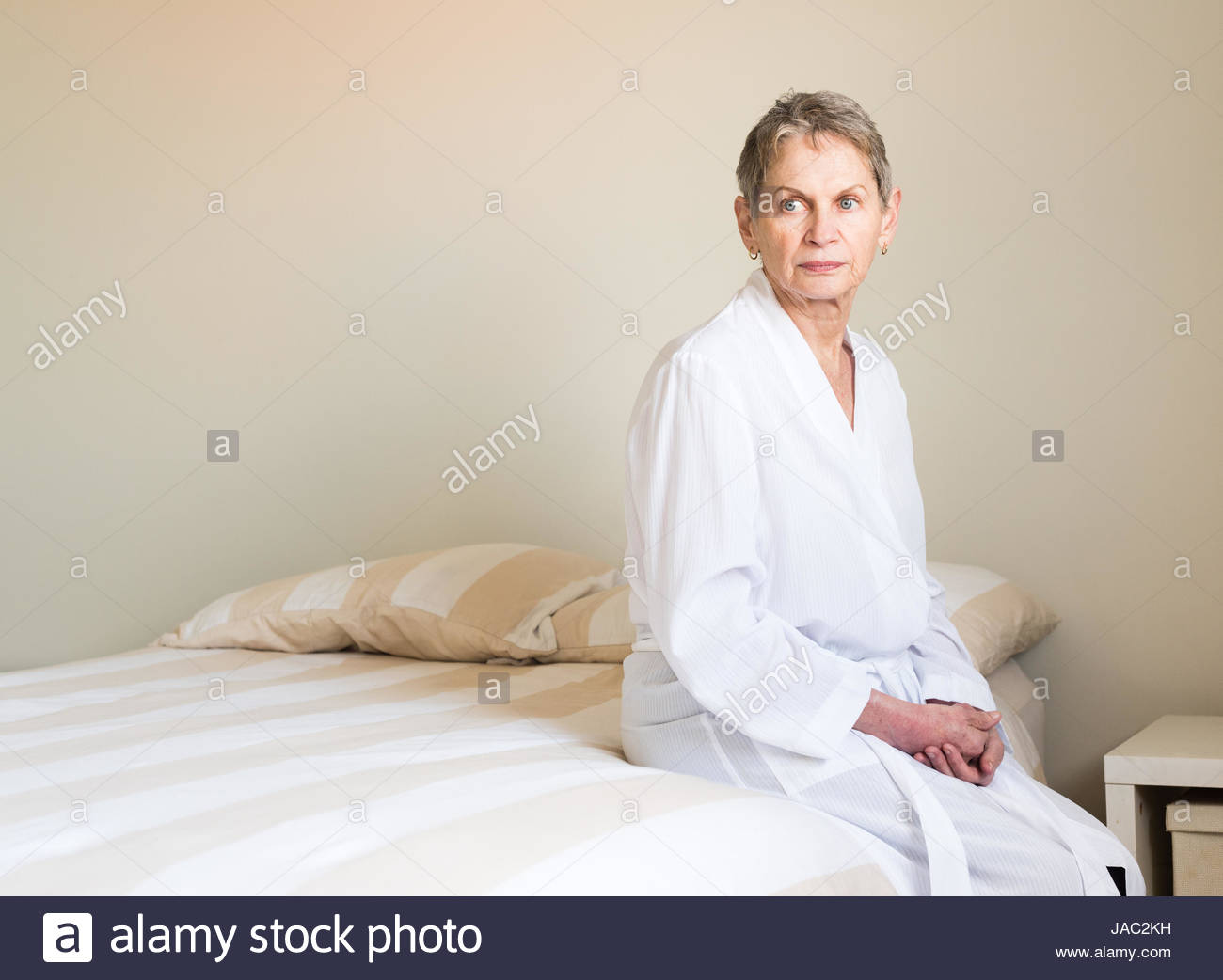 Elderly woman with short hair and white dressing gown seated on bed ...