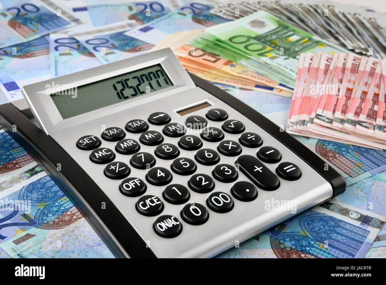 Ein eingeschalteter Taschenrechner liegt auf vielen Geldscheinen - Stock Image