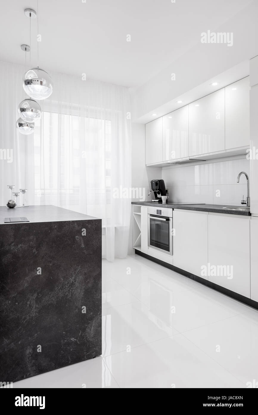White High Gloss Kitchen With Dark Island And Modern Lamps Stock Photo Alamy