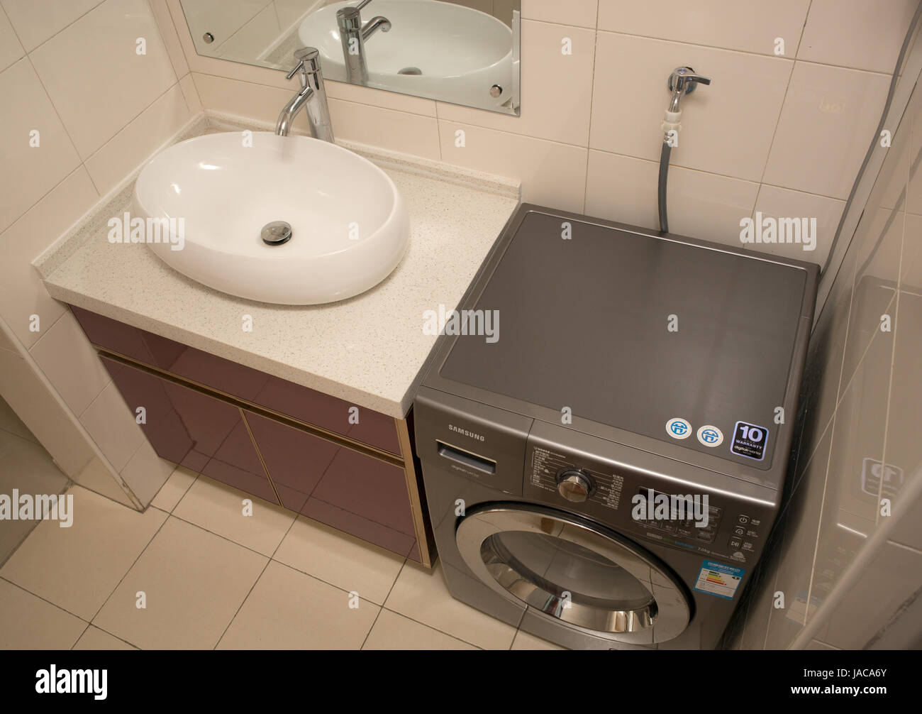 Wash basin, taps, and washing machine inside apartment. Nanjing ...