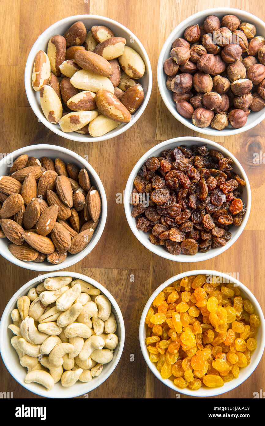 Various nuts and raisins in bowl on wooden table. Stock Photo