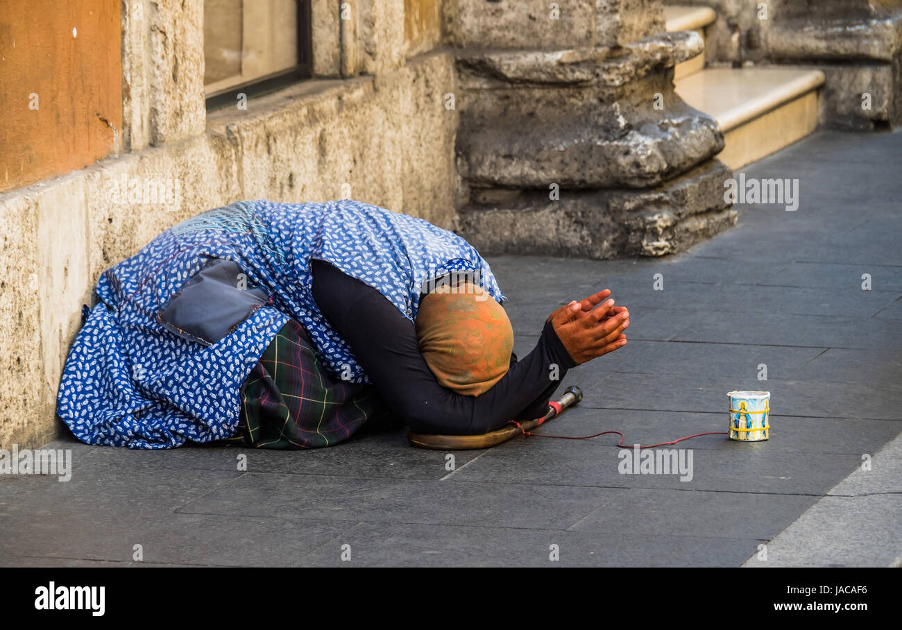 A beggar on the street. Anti-theft device by means of red cable, Eine Bettlerin auf der Straße. Diebstahlsicherung - Stock Image