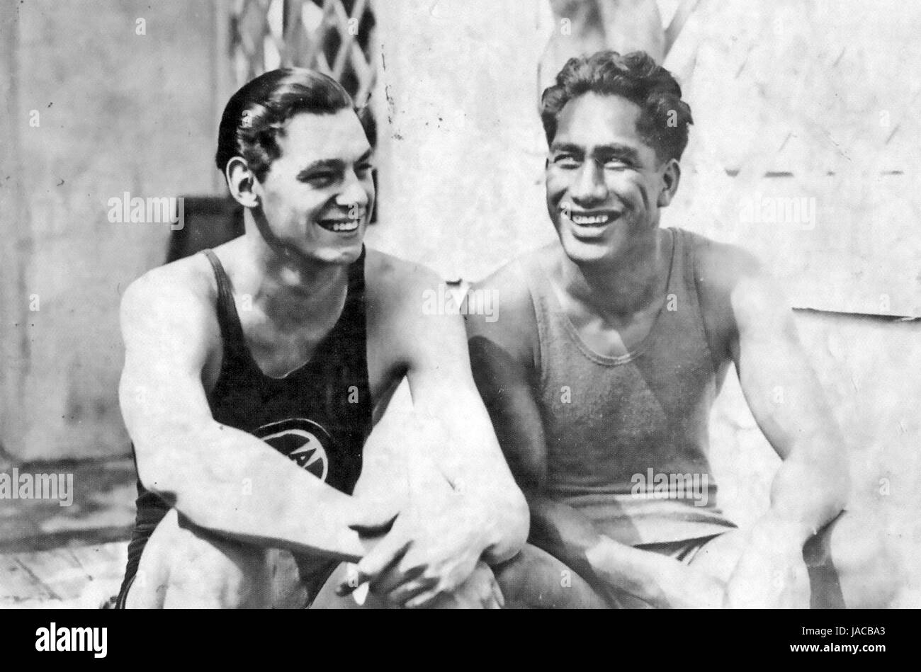 DUKE KAHANAMOKU Hawaiian surfer and Olympic swimmer at right with fellow American Olympian Johnny Weismuller about - Stock Image