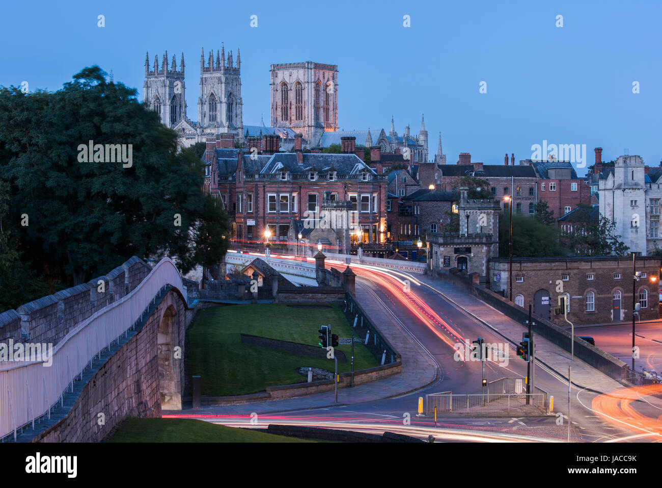 City walls, road over Lendal Bridge & 3 iconic towers of Minster set against dark evening sky, glow of street - Stock Image